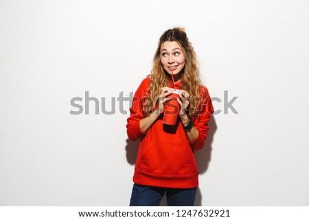 image of pretty woman 20s wearing red sweatshirt drinking soda f stock photo © deandrobot