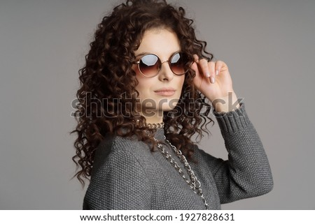 Image of european curly woman 20s wearing casual clothes holding Stock photo © deandrobot