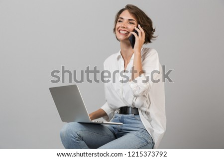 Happy young woman sitting on stool isolated over grey background holding newspaper reading. Stock photo © deandrobot