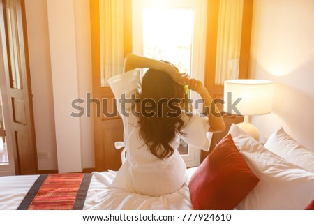 Attractive asian woman stretch oneself awaking on the bed room. Stock photo © snowing