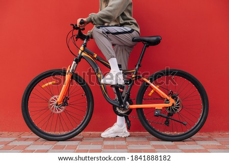 Photo of feminine woman standing with bicycle outdoors, during s Stock photo © deandrobot