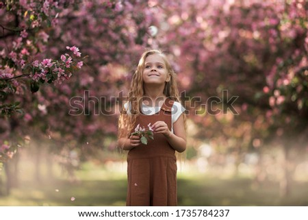A carefree walk in the blooming Apple orchard. The girl is blonde with long hair in a long dress. Stock photo © ElenaBatkova