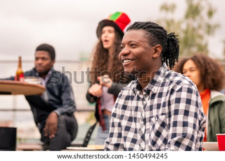Happy mixed-race guy in checkered shirt and his friends watching broadcast Stock photo © pressmaster