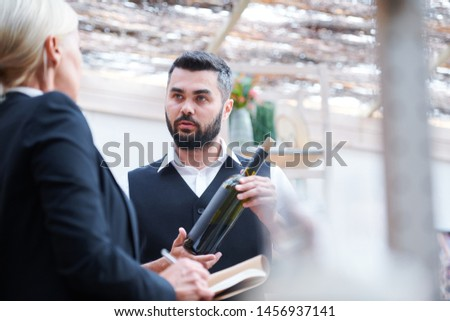 Young confident cavist with bottle of wine talking to his colleague Stock photo © pressmaster