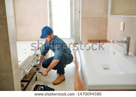 Young worker in uniform sitting on squats while fixing or fastening detail Stock photo © pressmaster