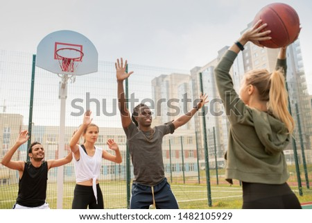 Group of intercultural students or friends in sportswear playing basketball Stock photo © pressmaster