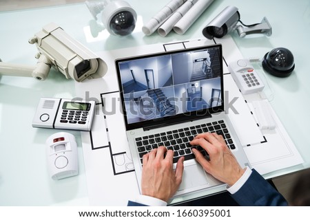 Watching Footage On Laptop With Security Equipment On Blueprint Stock photo © AndreyPopov