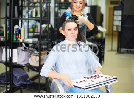 gorgeous happy woman looking to the camera while examining hair stock photo © dashapetrenko