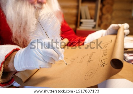 Gloved hand of Santa holding white plume over nice list on unrolled paper Stock photo © pressmaster