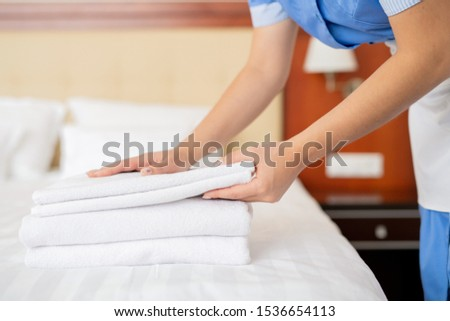 Hands of young contemporary chamber maid making stack of white fresh towels Stock photo © pressmaster