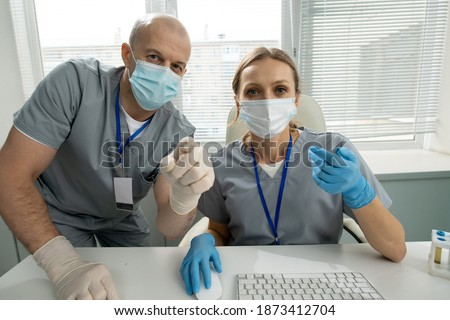 Clinician in uniform smiling at patient while pointing at medical document Stock photo © pressmaster