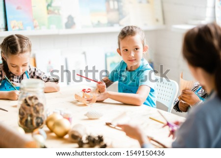 clever schoolgirl with crayon looking at teacher while listening to her advice stock photo © pressmaster