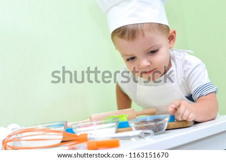 Little boy whisking flour with raw eggs in bowl by table while helping mom Stock photo © pressmaster