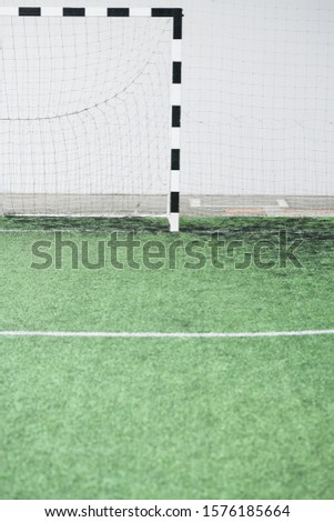 Part of green football field and gates with net against white wall at stadium Stock photo © pressmaster