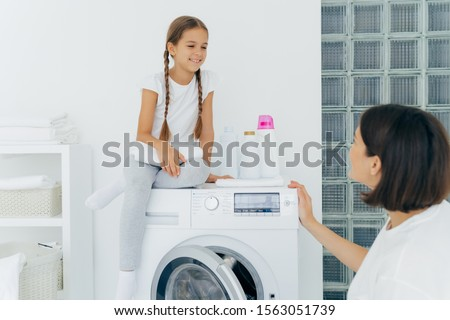 Adorable small girl with pigtails, poses on top of washer, holds white soft towel, looks gladfully a Stock photo © vkstudio