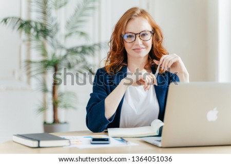 Positive red haired young female entrepreneur watches business webinar, writes email, makes notes in Stock photo © vkstudio