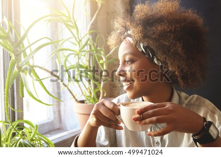 Headshot of attractive young African American woman holds modern cell phone near ear, has nice conve Stock photo © vkstudio