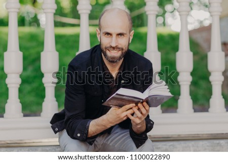 Positive bearded man looks directly into camera, reads very exciting and interesting book, sits agai Stock photo © vkstudio
