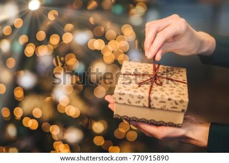 Felismerhetetlen nő ajándék doboz karácsonyfa ragyogó fények Stock fotó © vkstudio