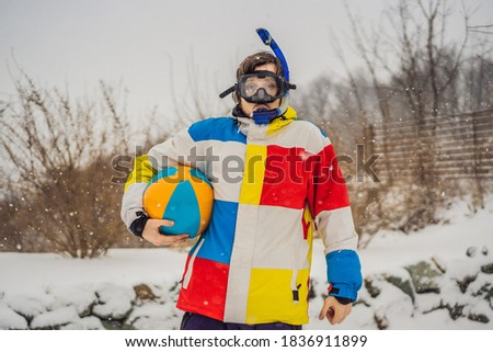 The man went outside in winter in snorkeling equipment and with a beach ball. A man dreams of a vaca Stock photo © galitskaya