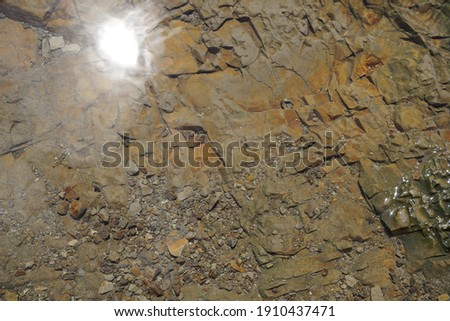 Rocks create a wall of stone in beautiful colors at water's edge Stock photo © Klodien