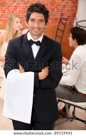 well dressed waiter facing the camera, behind a couple is dining at restaurant Stock photo © photography33