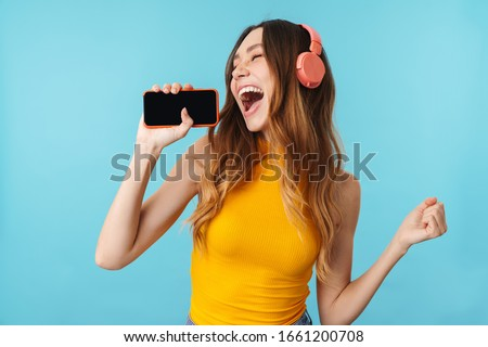 Delighted young woman listening to music with headphones lying on the grass stock photo © wavebreak_media