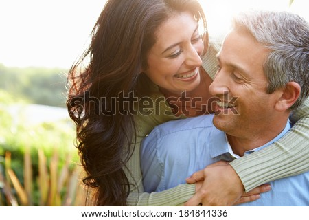 Man piggybacking woman outdoors smiling Stock photo © IS2