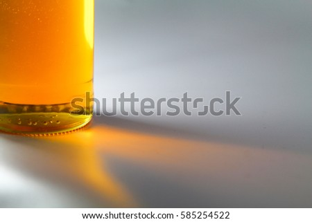 The glass transparent bottle with reflection on a yellow paper background. Stock photo © artjazz