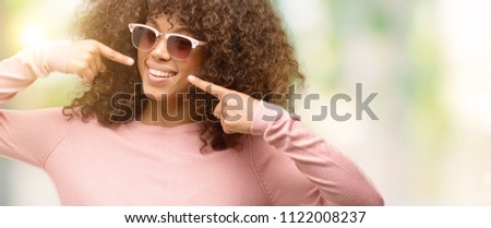 beauty smiling curly woman is wearing pink sunglasses and eating stock photo © dashapetrenko