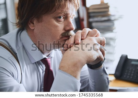 The man is sitting in the office at the desk, holding a calculator in his hand, supports the phone w Stock photo © Traimak
