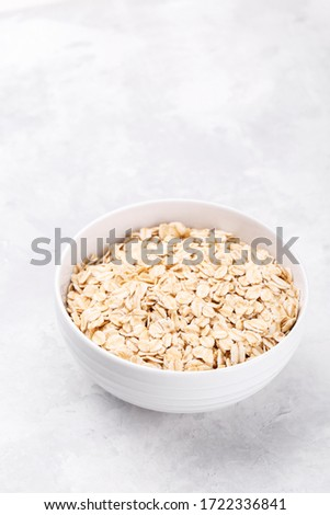 Uncooked oat flakes in a white bowl on a gray background. Close up, top view of natural organic prod Stock photo © artjazz