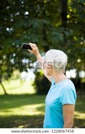senior woman taking selfie in the park after workaout stock photo © boggy