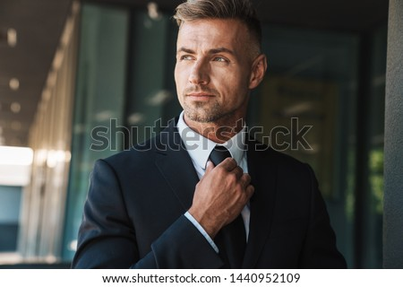 Photo of attractive man in businesslike suit working on laptop i Stock photo © deandrobot