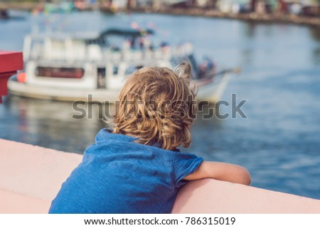 The boy admires the sea and colourful boats moored at Phu Quoc Vietnam. Boats such as these are icon Stock photo © galitskaya