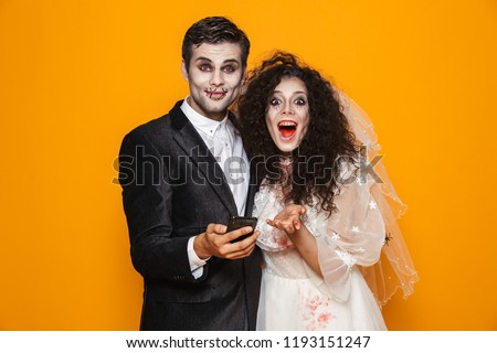 happy dead bride looking camera and holding smartphone isolated stock photo © deandrobot