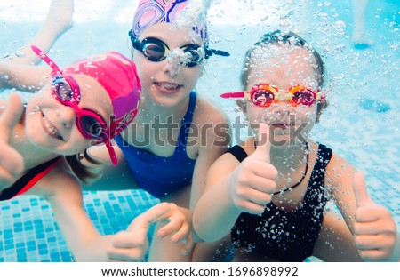 Stock photo: A child boy is swimming underwater in a pool, smiling and holding breath, with swimming glasses