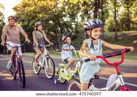 Família feliz equitação bicicletas ao ar livre sorridente mamãe Foto stock © galitskaya