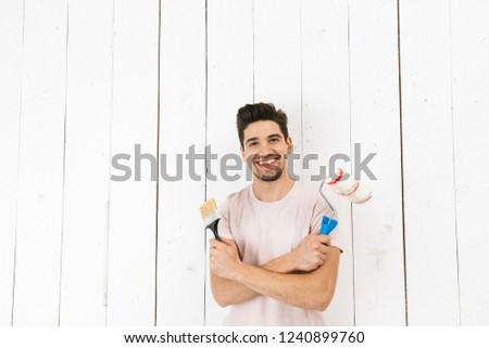 Image of handsome man 20s painting white wall and making renovat Stock photo © deandrobot