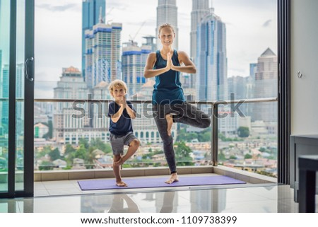 Mom and son are practicing yoga on the balcony in the background of a big city. Sports mom with kid  Foto stock © galitskaya