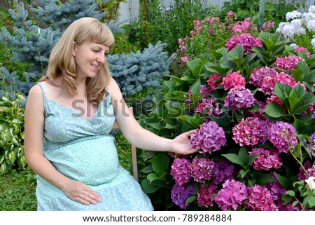 A pregnant woman in late term pregnancy in the garden of Wisteria in bloom hugs the belly Stock photo © ElenaBatkova