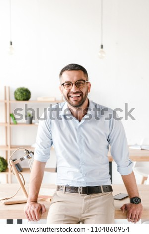 Image of smiling employer guy in white shirt sitting in office a Stock photo © deandrobot