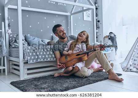 young father teaching his little daughter to play guitar while s stock photo © boggy