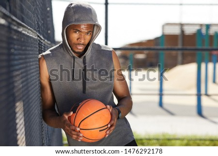Young contemporary male basketball player holding ball by his face and chest Stock photo © pressmaster