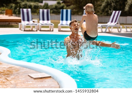 father and son in outdoor swimming pool with city view in blue sky vertical format for instagram mob stock photo © galitskaya