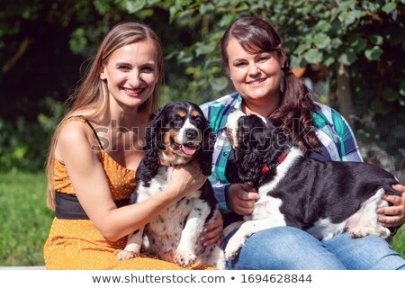 Two girlfriends having fun with dogs in the animal sanctuary Stock photo © Kzenon