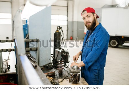 young bearded repairman using wrench or other handtool to fix parts of engine stock photo © pressmaster