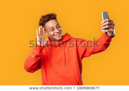 young man in red hoodie calling on smartphone Stock photo © dolgachov