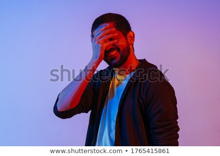 man covering his mouth by hand in neon lights Stock photo © dolgachov