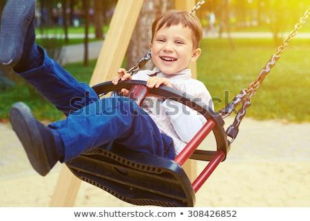 Szczęśliwy mały chłopca jazda konna huśtawka parku Zdjęcia stock © galitskaya